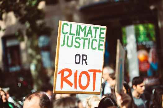 climate justice or riot banner